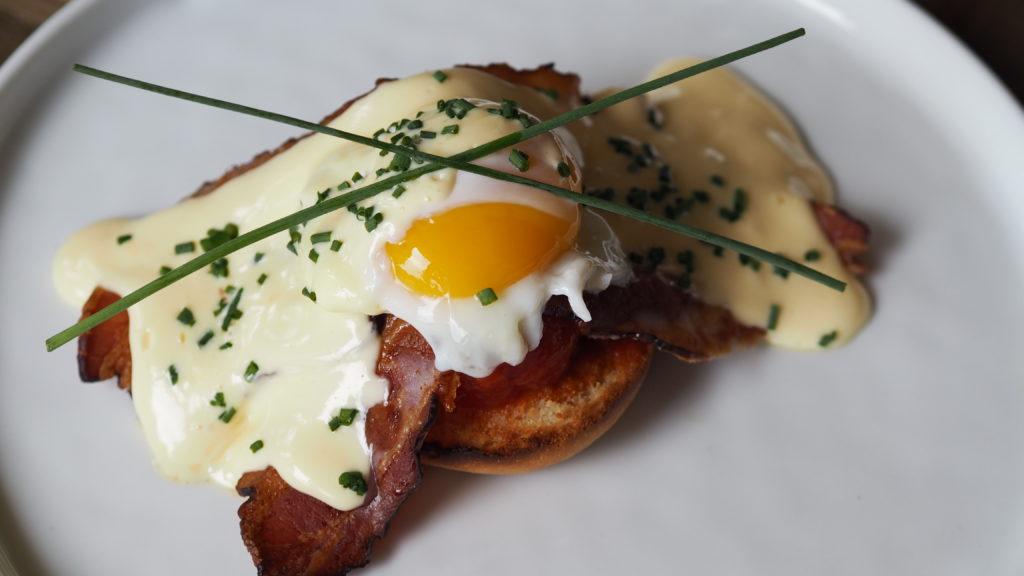 Ultieme Eggs Benedict met hollandaise, bacon, brioche en bieslook