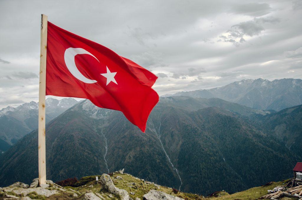 Turkse vlag, vier wapperend op een bergtop, boven de bergen uit.