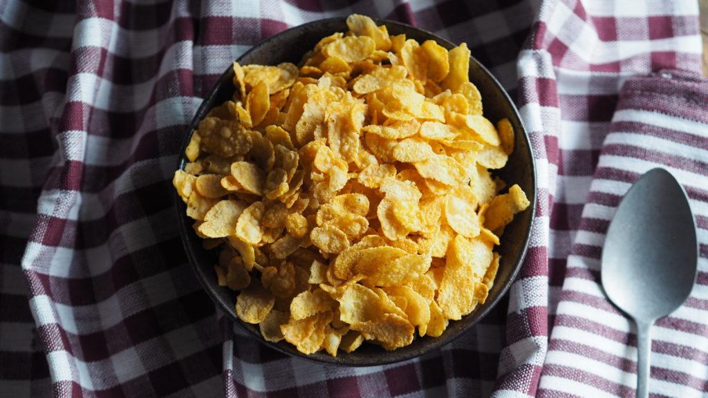 Kom met cornflakes, oude lepel op een bordeauxrode geblokte en gestreepte achtergrond.