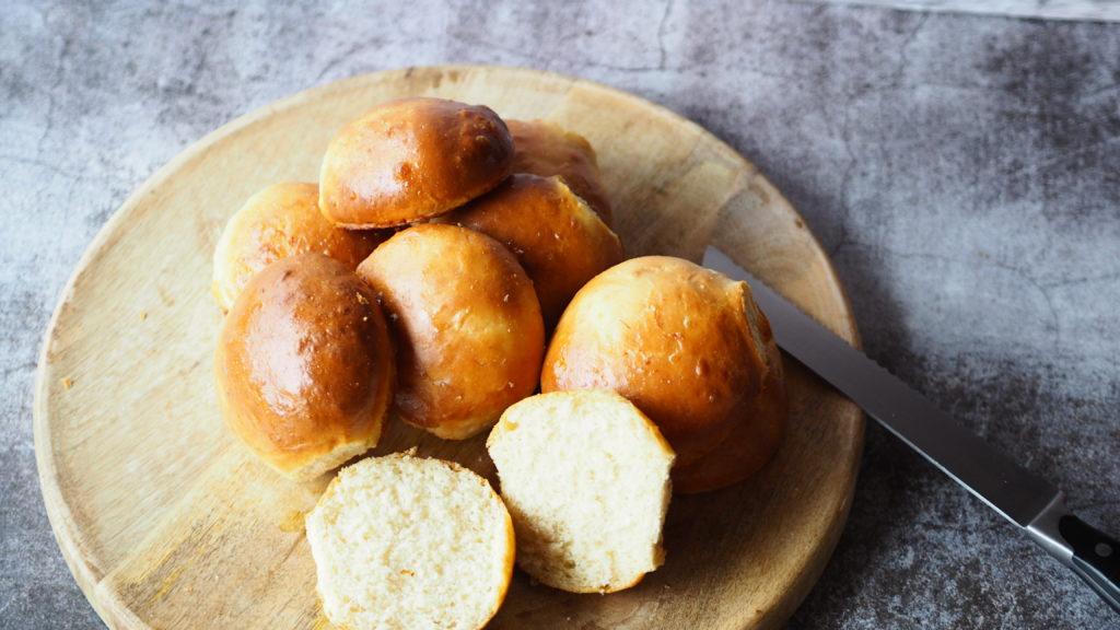 brioche bollen op een houten ronde plank met broodmes.