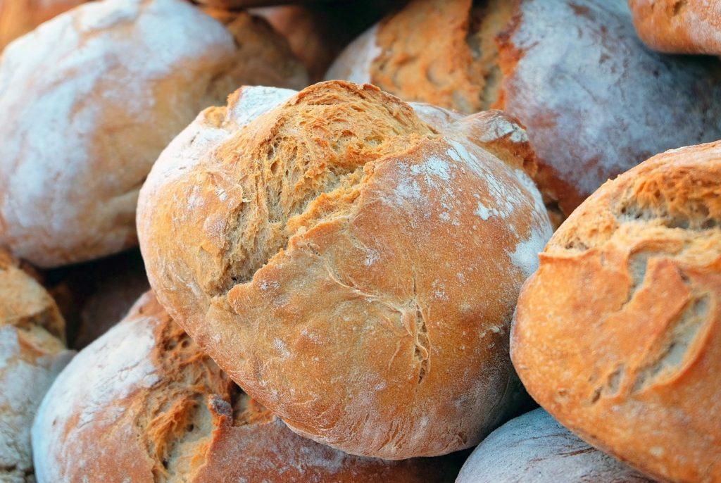 Brood: verschillende brood bollen, broden, op een stapel, mooi afgebloemd en gebarsten.