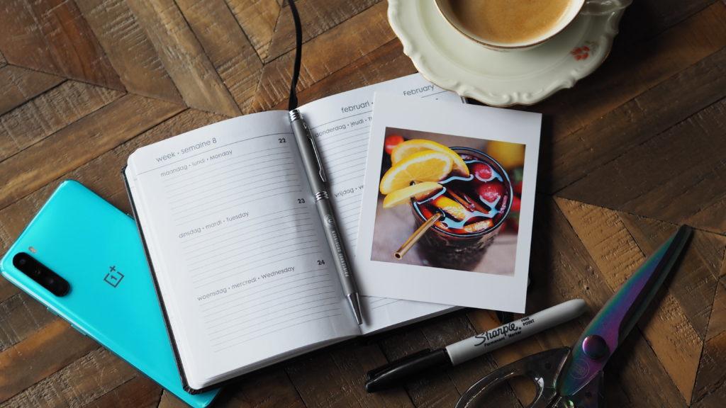 foto's van fotofabriek bij een agenda, pen, sharpie, kopje koffie en oneplus Nord smartphone