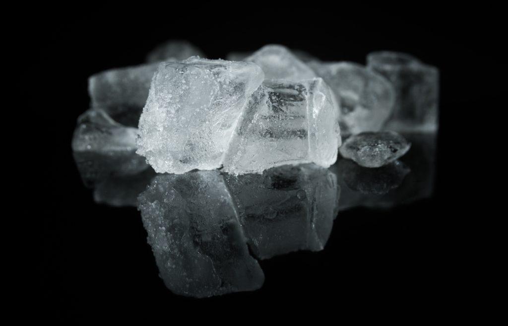 ijsblokjes op een zwarte, spiegelende achtergrond