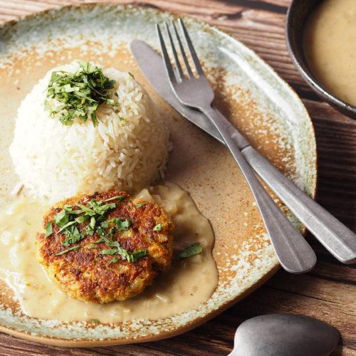 boekoeloekoe met groene curry en gemberrijst - week zonder vlees. Houten achtergrond, oudzilveren bestek