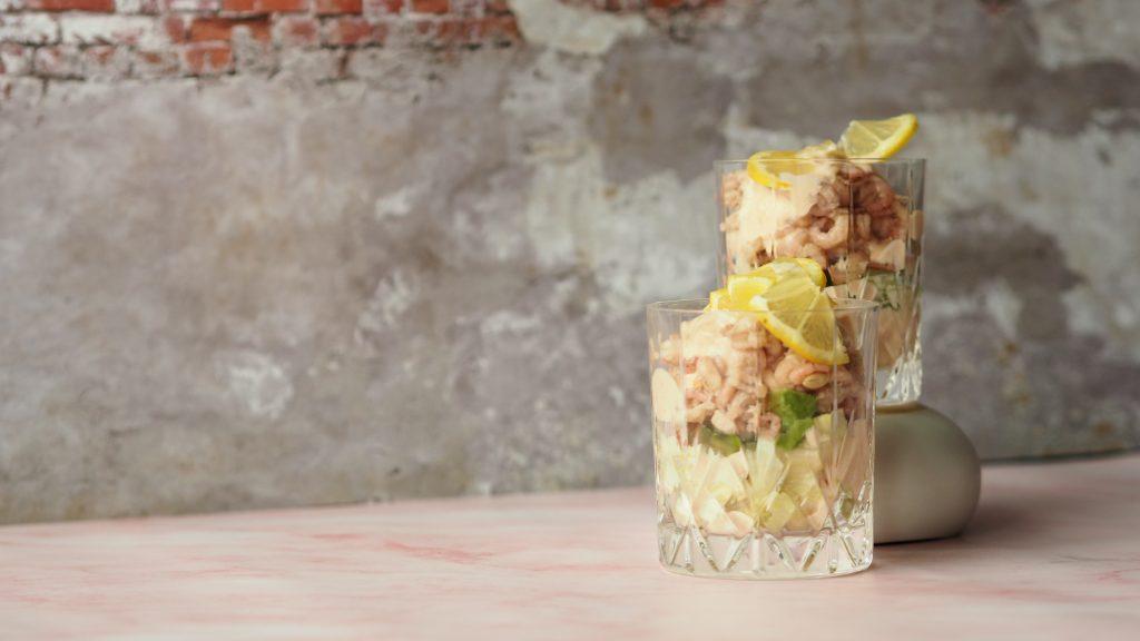 garnalencocktail 2 maal in een kristallen glas met een citroentje tegen een roze, betonnen achtergrond