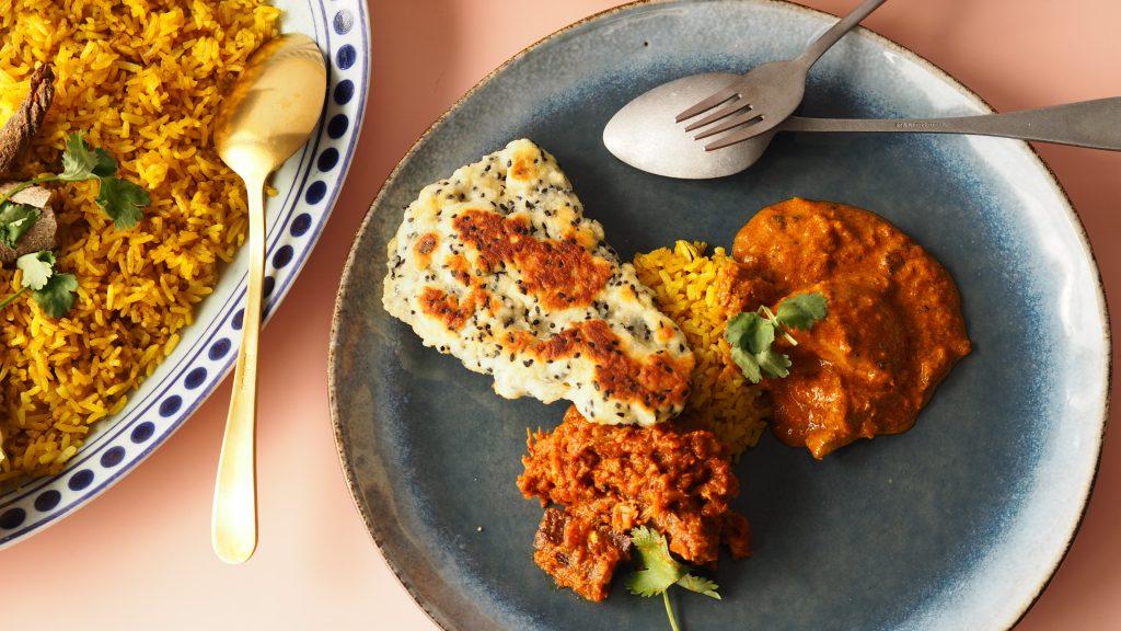 butter chicken met ander schalen eten een tafel voor indiaas eten tegen een roze achtergrond