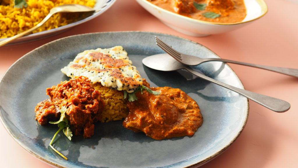 naan broden op een roze achtergrond met theedoeken en nigella zaad met curry op blauw servies en bestek