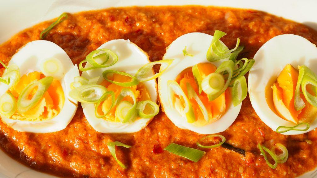 sambal goreng telor table top in saus eieren, op roze achtergrond