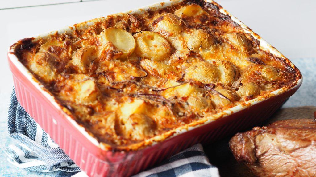 aardappel gratin op een blauw wit geruite theedoek, met ossenhaas chateaubriand en sjalotten saus