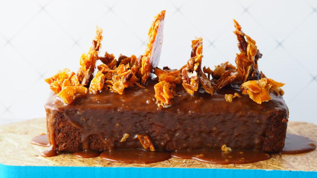 bananenbrood op een hardboard blauw plank tegen een witte achtergrond met karamel pecan cornflakes